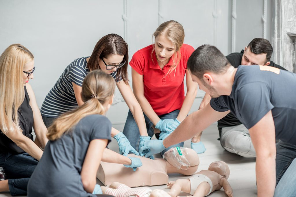 Group of people learning how to make first aid heart compressions with dummies