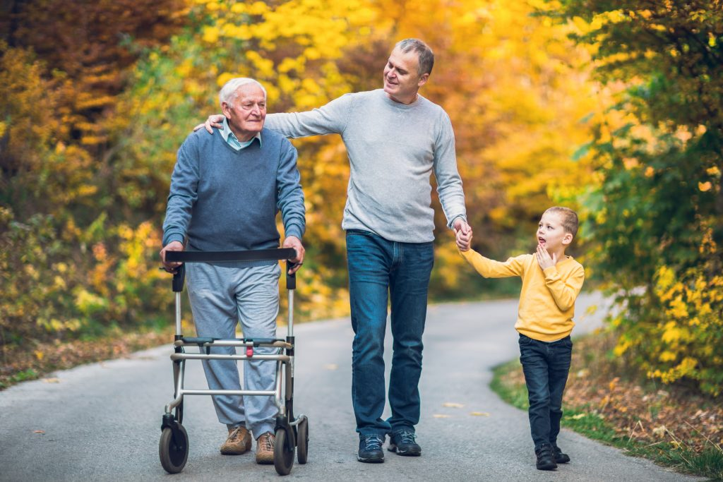 An elderly father with a walker, adult son and grandson out for a walk in the park